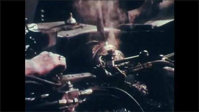 1970s: Man working at complex industrial machine. Machine smoking, sending out spirals of thin, shaved metal.