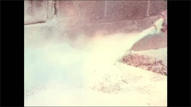 """1970s: Magnesium metal shavings on concrete floor catch fire, fire sparks and catches rapidly. Man uses fire extinguisher on concrete. Chart """"Classes of Fires"""" with A, B, C, D."""
