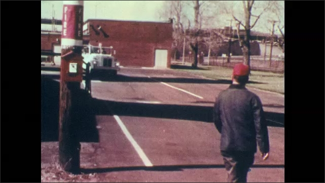 1970s: Man opens fire alarm, removes phone. Man runs to fire alarm box on telephone pole, triggers switch inside box. Man runs towards approaching fire truck and points. Man uses fire alarm in office.