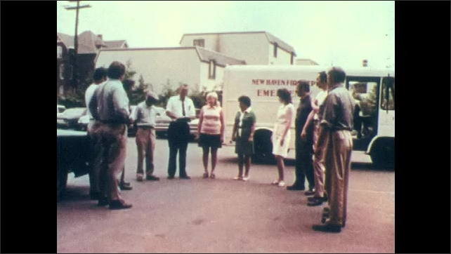 1970s: People exit building walking in straight line. People stand in parking lot in circle, one man reads from clipboard. Firefighters spray water on burning building at night.