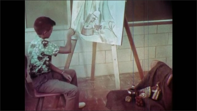 1960s: Boy sits at desk, looks through microscope, writes in notepad. Boy sits in front of easel, draws. Students sit at table in classroom, girl hands paper to girl, girl points at chalkboard.