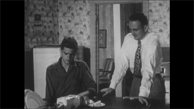 1950s: Man in kitchen removes suit jacket and begins making a sandwich. Pensive teen boy enters kitchen and man offers to make him a sandwich. Boy sits down heavily as man begins to demonstrate.