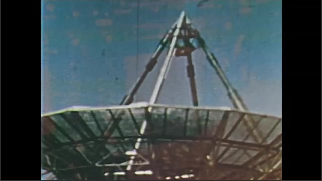 1960s: UNITED STATES: men follows inflation of sphere during rocket launch. Trinidad at work during space flight. Satellite dish on ground