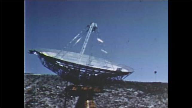 1960s: UNITED STATES: man speaks on telephone. Satellite dish on ground. Man speaks on phone. Close up of speaker
