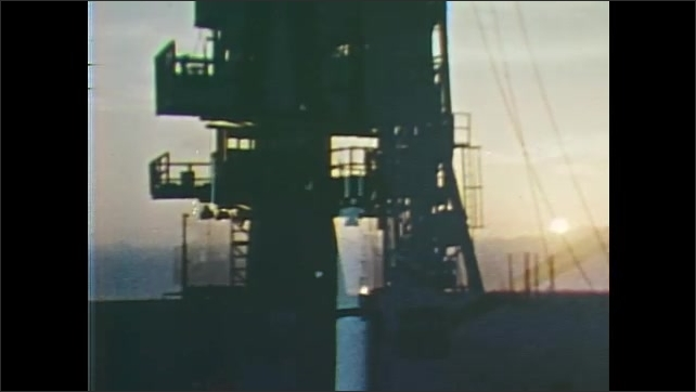 1960s: UNITED STATES: launch pad at sunrise. Men work at control panel. Rocket on scaffold
