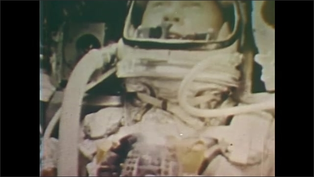 1960s: Glenn excitedly narrates. View of deployed chute through capsule window as sky rushes by. Mission control people stand. Boat rushes to pick-up spot in ocean.