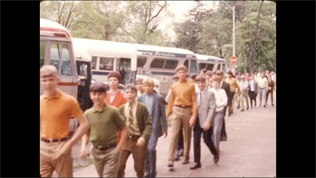1970s: Advertisement of historical North Carolina exhibit. Group of students walk past row of buses. N.C. State Capitol.