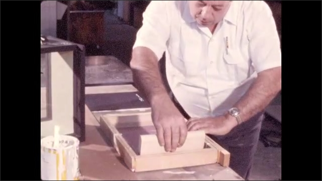 1970s: Man saws wood on table saw. Man hammers nail into wood structure. Man uses silkscreen to print words on an exhibit label.