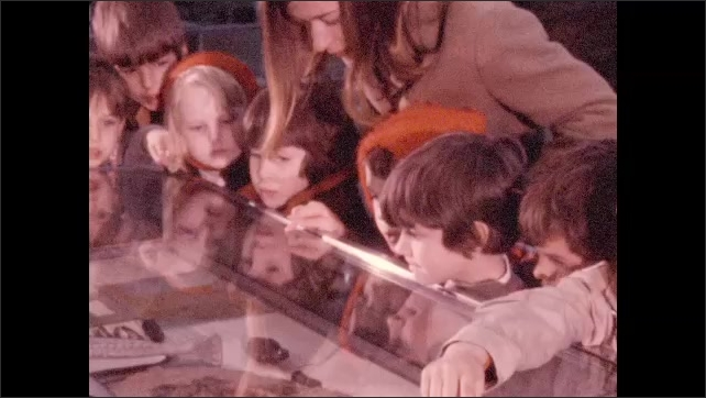 1970s: View of dinosaur skeleton. Students in classroom watch man who is holding a snake. Young students and adult crowd around glass display case and look at snake.
