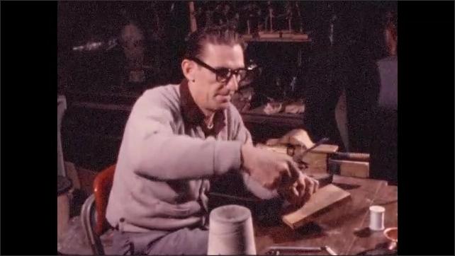 1970s: Man winds thread around stuffed bird mounted on board.