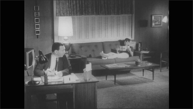 1950s: Father sits at desk going through papers. Boy sits on couch reading pamphlet. Father talks to son, son walks over to show him something.