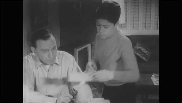 1950s: Hand points to columns on chart of goals. Father sits at desk, talks, son stands, listens, picks up paper, points. Father does long division on notepad.