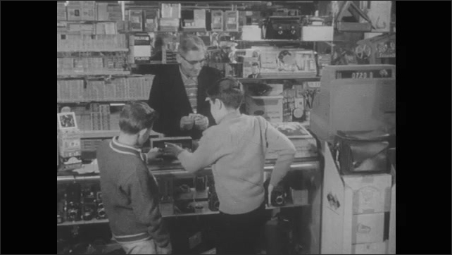 1950s: Two boys stand at shop counter. Boy pulls cash out of wallet, hands to shopkeeper who counts cash. Boy pretends to take photo with camera, shakes head, hands camera to other boy.