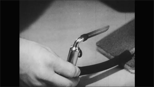1940s: Hand presses on air bladder of medical apparatus. Hands remove and display metal reed in medical device. Hand places device in various lengths of glass tube.
