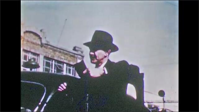 1950s: Parked cars.  Men talk to police officers.  Men gesture.