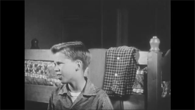 1950s: Boy dries himself off with towel after taking shower. Woman looks at clothes on boy's bed. Boy puts on clothes, combs hair.