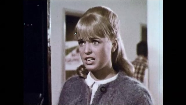 1960s: Young woman holding cake speaks to girl by lockers.