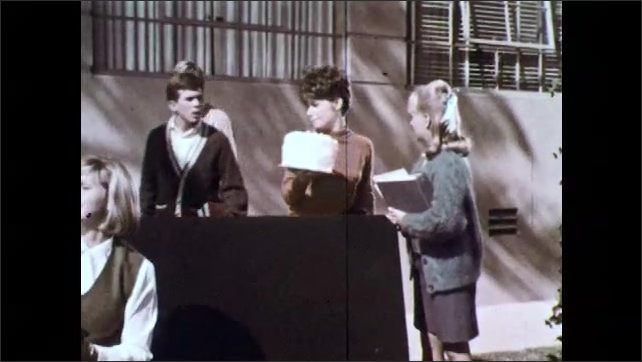 1960s: Young men walk down stairs; young man throw his arms in the air. Young man gestures and speaks. Boys walk past girls with cake and stop. Boys and girls speak. Girl holds out papers.