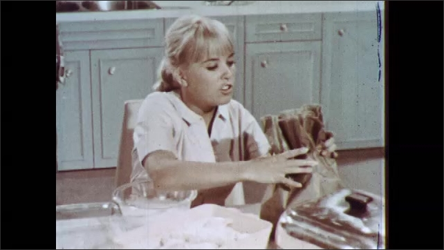 1960s: Young woman dips chicken in bowl of milk, places it in paper bag, shakes the bag, and removes the chicken from the bag.