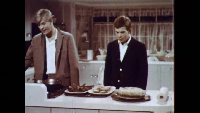1960s: Boys speak as boy takes chicken out of pan and places it on platter. Boy adjusts jacket.