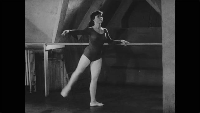 1950s: Girl dancing at ballet barre. View of feet, tilt up girl dancing.