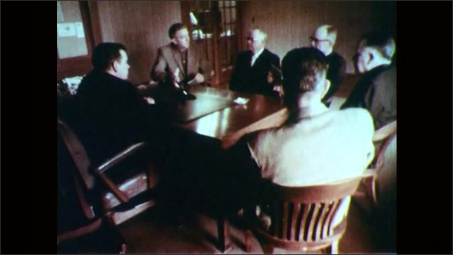 1960s: Men sit around conference table, talk.