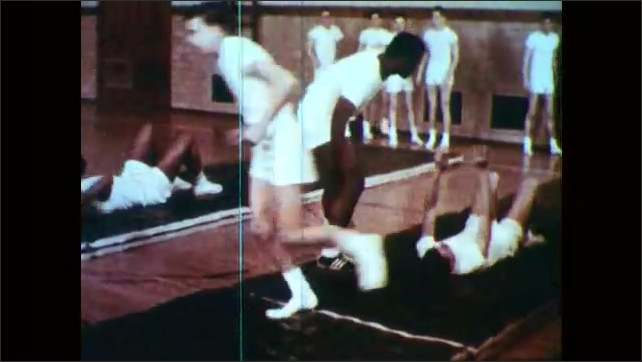 1960s: Boys on bench lift weights. Boys flip and tumble down mats and over other students. Girls in leotards do a dance.