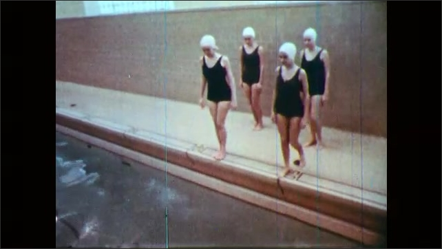 1960s: Boys crawl on gym floor. Girls in swimsuits and caps stand on side of pool. Girls dive into pool.