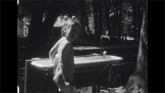 1940s: Tall trees in forest. Girl stands next to outdoor tub filled with water. Rollercoaster.