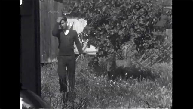 1940s: Woman looking in trunk of car. Boy runs by tree. Boy follows him. Girl runs by. Woman walks by holding cake.