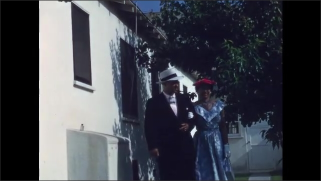 1950s San Francisco: Passengers including woman holding baby board airplane. Woman in a dress and man in a suit walk in slow motion up to house