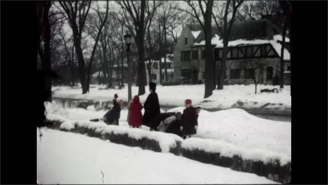 1960s California: Line of kids on sidewalk with woman. Views of woman with kids. Girl running, holding box. Kids getting into car.