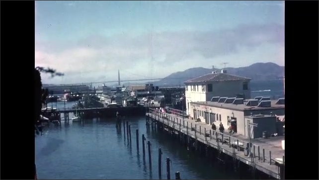 1960s: Chinatown in San Francisco. Buildings in Chinatown. Fisherman's wharf. Boats docked at marina.