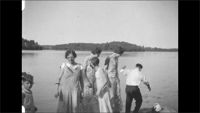 1930s: People stand on shore of lake. Women wave, wade into water.