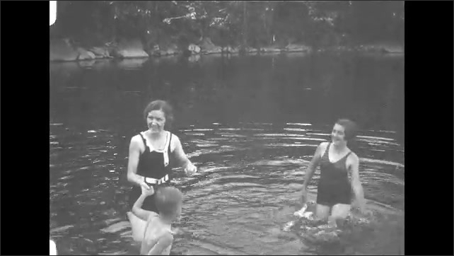 1930s: Woman splashes and plays with children in lake.