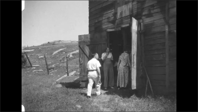 1930s: Pile of rocks. Women open barn doors. Women and man peek into barn. Men and women walk down road.