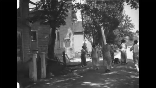 1930s: People walk down road.