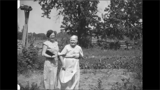 1930s: Two women stand together outside and talk. Children join women, family poses.