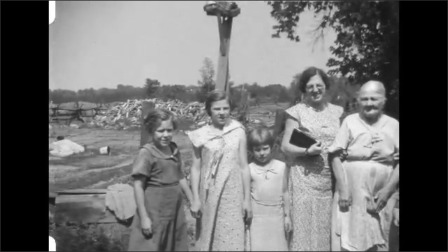 1930s: Women and children stand together outside, pose for camera, smile.