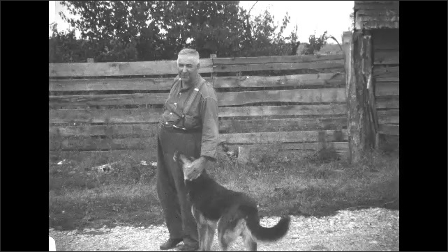 1930s: Man walks around outside on gravel road, pets dog.
