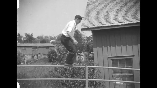 1930s: Man balances on top of fence, falls down, climbs back up. Boat travels across water.