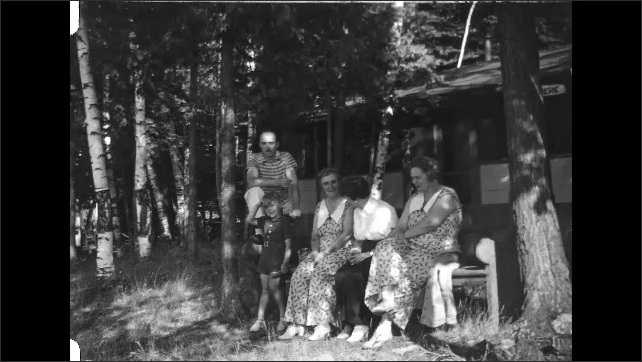 1930s: People sit on bench in front of house.