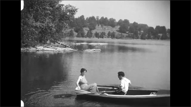 1930s: Man and woman sit in rowboat, man rows boat.