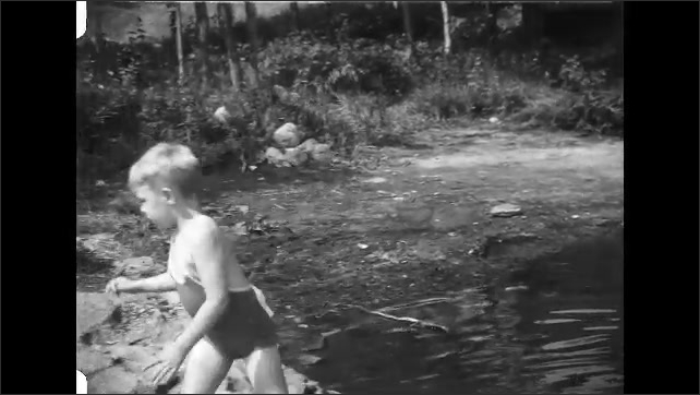 1930s: Boy wades into water, splashes. Man looks out at water, holds net. House.