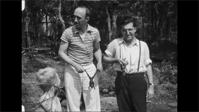 1930s: Men stand outside, hold frogs. Little boy holds net. Men compare frogs.
