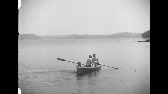 1930s: Woman sits on shore, people sit in boat. Man rows boat onto lake, boy splashes in water.