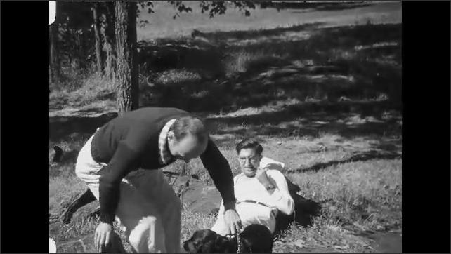 1930s: Men sit by lakeshore. Man pets dog.