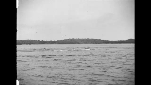 1930s: Dog rides on boat, boat travels across water. Boat pulls waterskiier, waterskiier falls in water.