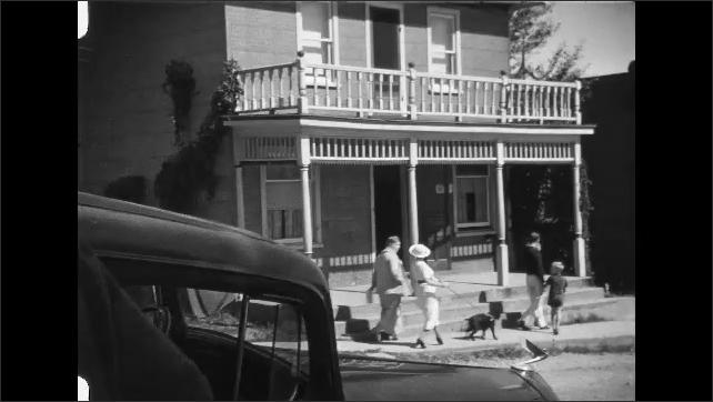 1930s: People walk down sidewalk in small town.