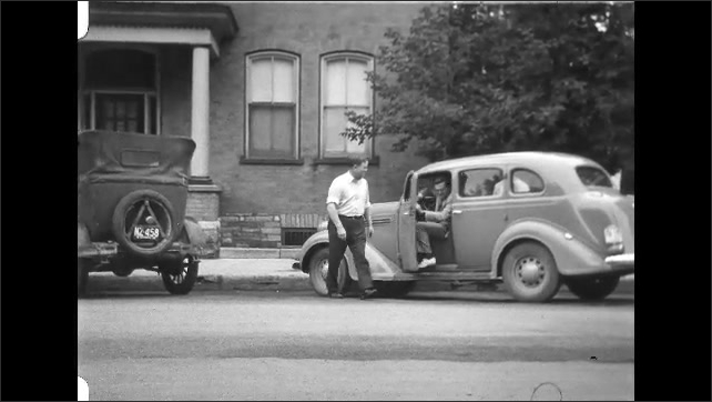 1930s: Man walks to car, shakes hands with man in car. Man exits car, men walk across the street.